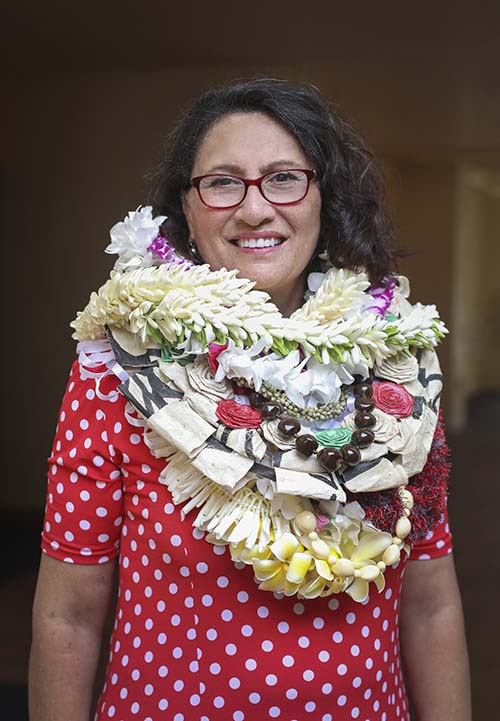 Polynesian woman wearing several flower leis