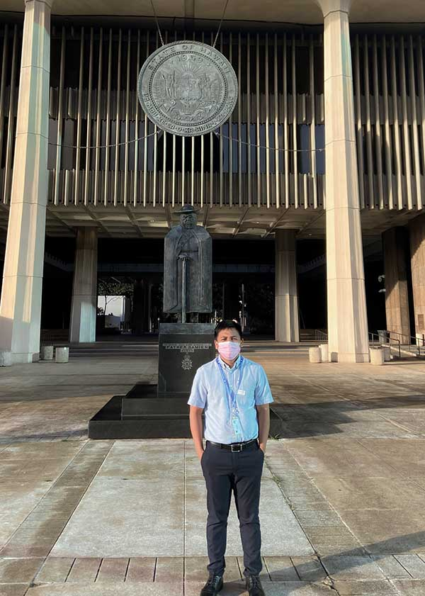 Filipino man standing in front of the Hawaii State Legislature