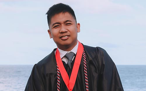 Filipino man wearing graduation gown