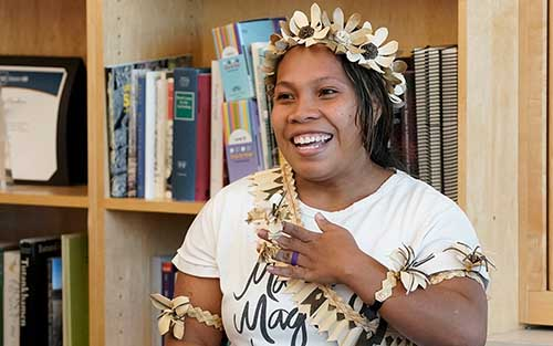 A Micronesian women, wearing flowers on her arms, over her shoulder, and in her hair, with one hand over her heart as to indicate gratitude.