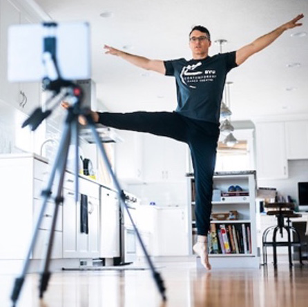 A male instructor demonstrates a dance move to in front of a camera on a tripod.