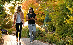 Two female students wearing masks walking on campus with trees in fall colors.