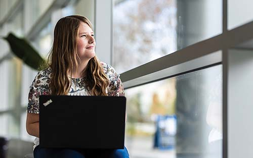 Emily Neiderhauser with her laptop by a window in the Joseph F. Smith Building.