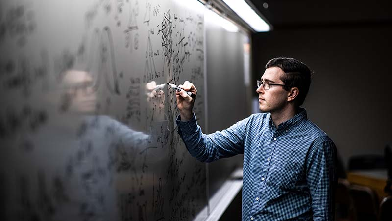 BYU math student works on an equation on a whiteboard.