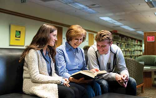 Judy Garvin reads a book with two students in the Harold B. Lee Library.