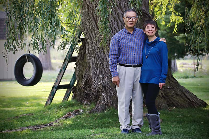 Knight Society members Ray and Yukiko Matsuura in front of a large tree with a tire swing and ladder.