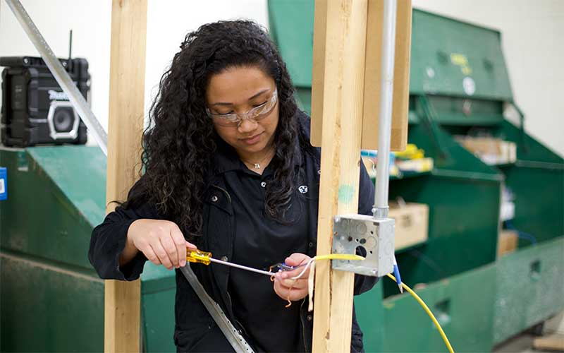 Female student with safety goggles using a screwdriver to wire a house frame.