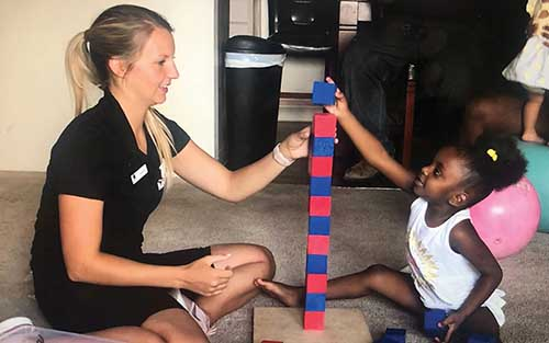 A BYU student builds a block tower with a young girl.