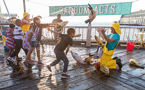Children spray water and play with rubber fish on a waterfront with some adults.