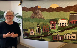 woman standing by a quilt she made that visualizes the history of Ensign College in honor of the college's new name.