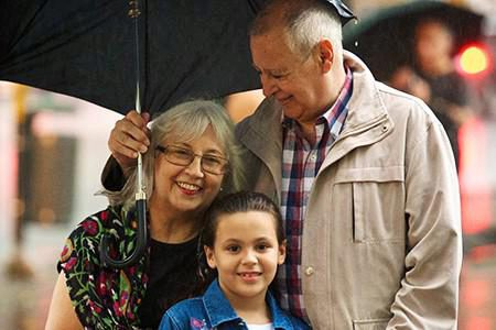 Grandparents holding an umbrella with their granddaughter