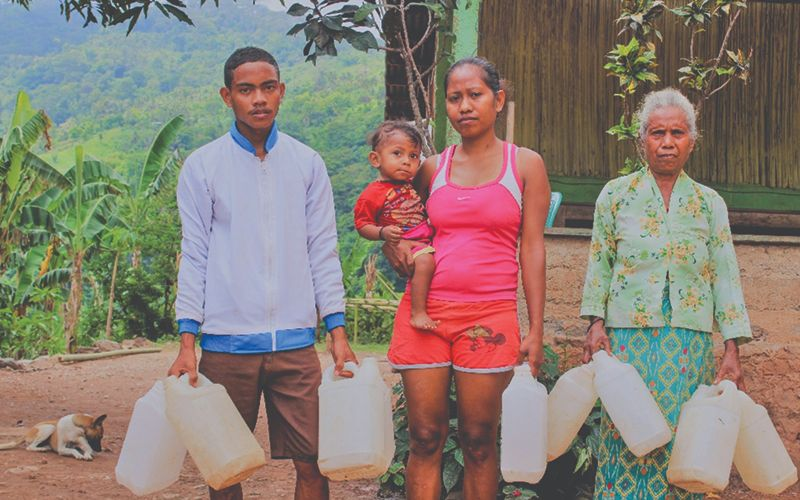 Photo of two women, a man, and a baby. They stand outside near a clean water well.