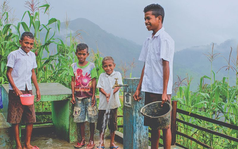 Four boys standing outside filling containers with clean water running from a faucet.
