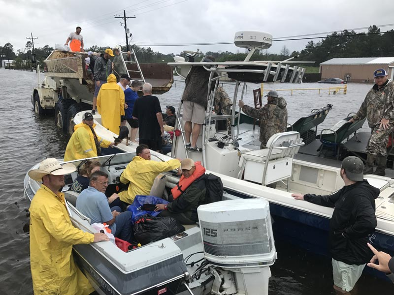People wearing rain slickers help others into boats
