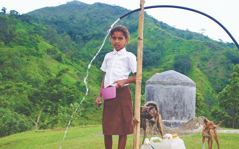 Young girl stands outside near a rubber hose filling her cup with clear running water.