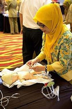 A midwife practices tying the umbilical cord on a baby simulator.