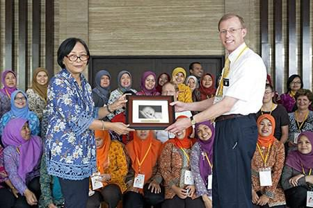 Dr. Visick presents a gift to Dr. Eriyati in front of 600 midwives