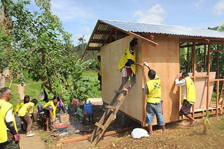 Volunteers nail plywood to the wooden frame of a house under construction in Tacloban, Philippines.
