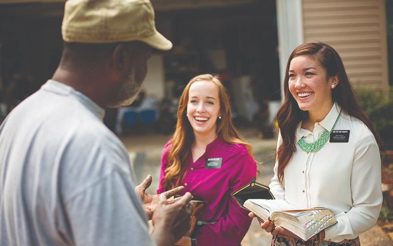 Two Sister Missionaries holding open scriptures and talking to a man outside of his home.